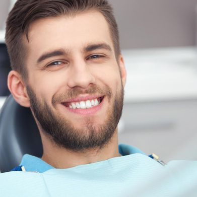 A man smiling while waiting for the dentist